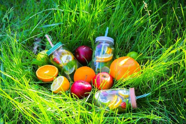 ストローの瓶に新鮮なレモネード。流行に敏感な夏の飲み物は、屋外の緑の芝生でフルーツと一緒に飲みます。自然の中で環境にやさしい。ガラスにミントが入ったレモン、オレンジ、ベリー。健康的なビーガンライフスタイル。