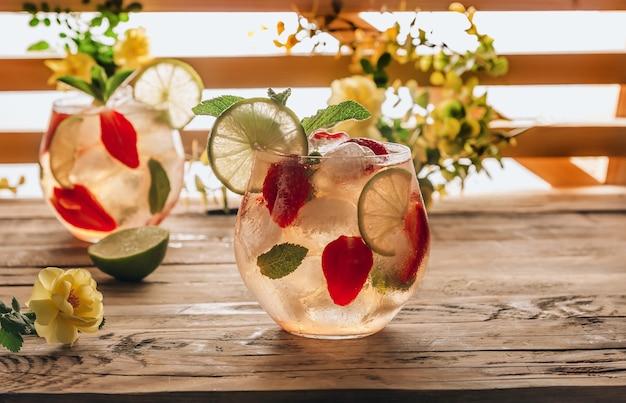 グリーン ティー ライム ミントとイチゴを木製の背景に入れた新鮮なレモネードは、寒い夏にベリー アイス ティーのセレクティブ フォーカス バックライト付きのグラスを 2 杯飲みます