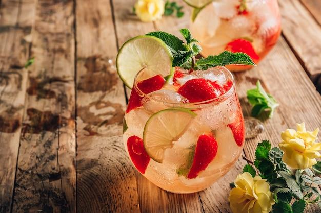 グリーン ティー ライム ミントとイチゴの木の背景に新鮮なレモネードは、ベリー アイス ティーのセレクティブ フォーカスで 2 つのグラスを飲みます。