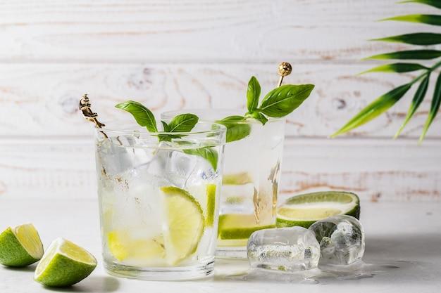 Свежий лимонад с кубиками льда, листьями лайма и базилика