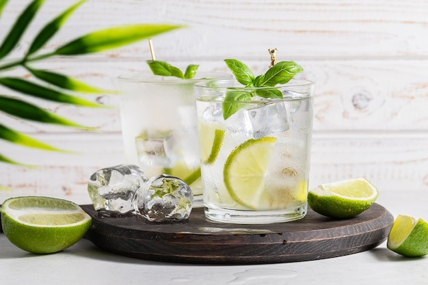 Fresh lemonade with ice cubes, lime and basil leaves on white wooden background refreshing summer cocktail on the table