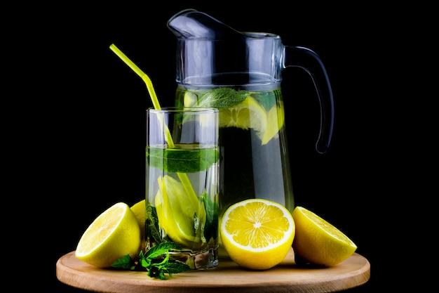Свежий лимонад с лимоном на деревянных фоне.