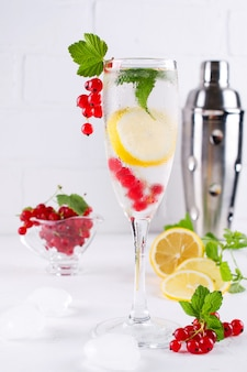 Fresh lemonade with lemon and red currant on white background