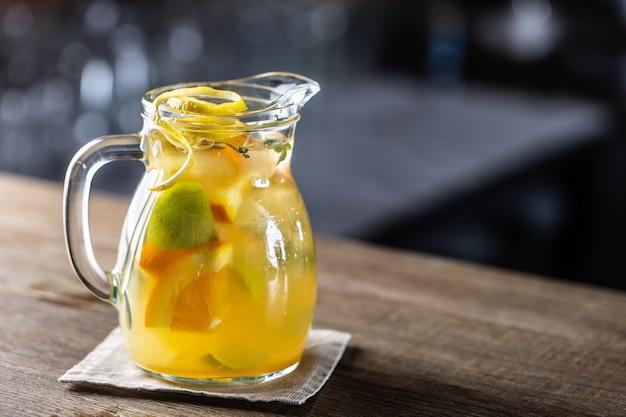 新鮮なフルーツのくさびが入ったフルジャーにさまざまな柑橘類が入った新鮮なレモネード。