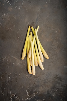 Fresh lemongrass herb on dark background with copy space. top view.