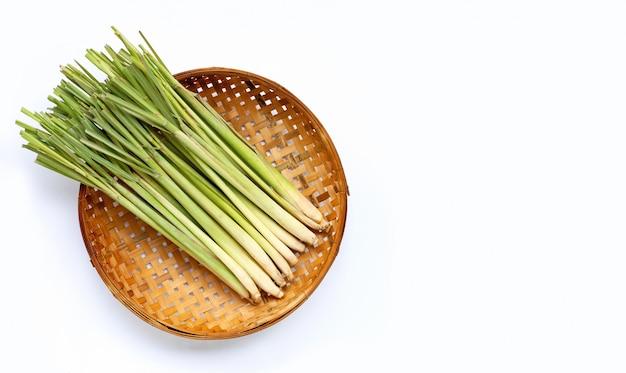 白い背景の上のバスケットを脱穀木製竹で新鮮なレモングラス。
