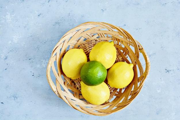 新鮮なレモンとライム、青色の背景にバスケットに。かんきつ類の果実。
