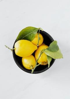 Fresh lemons in a black bowl