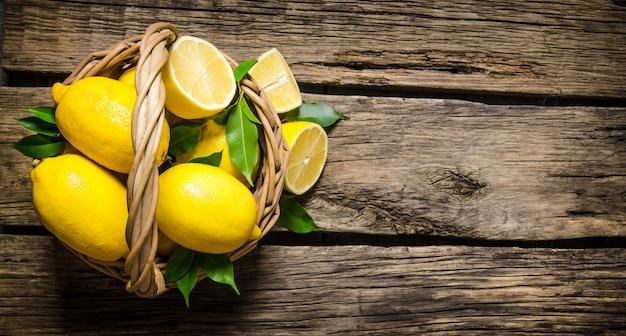 Свежие лимоны в корзине с листьями. на деревянном фоне. свободное место для текста. вид сверху