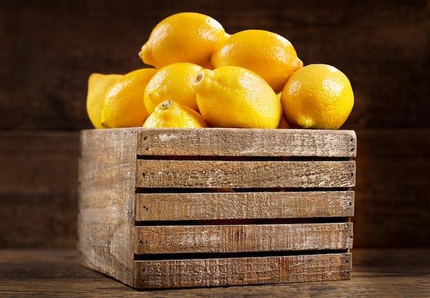 나무 배경에 나무 상자에 신선한 레몬