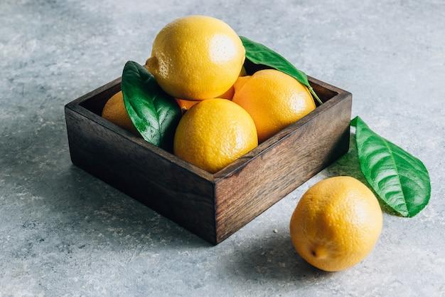 밝은 회색 배경에 잎을 가진 오래 된 상자에 신선한 레몬.