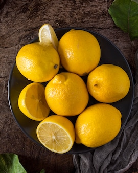 Свежие лимоны в миске сверху