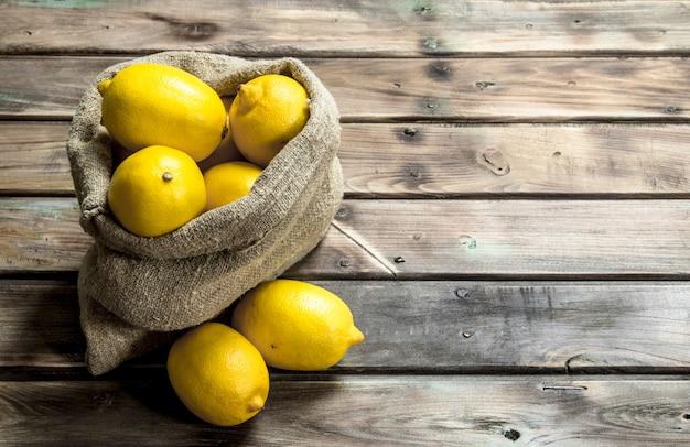 Свежие лимоны в мешке. на деревянном столе