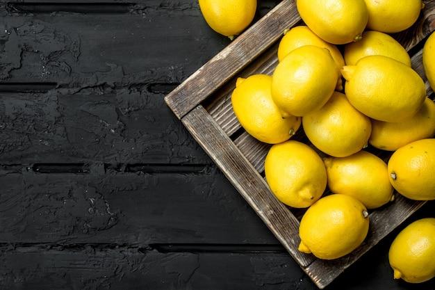 トレイに新鮮なレモン。黒の素朴な背景に