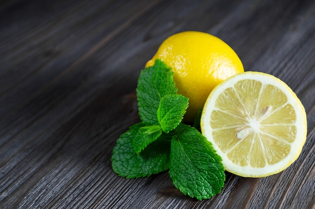 Fresh lemons and mint leaves on dark wooden table.