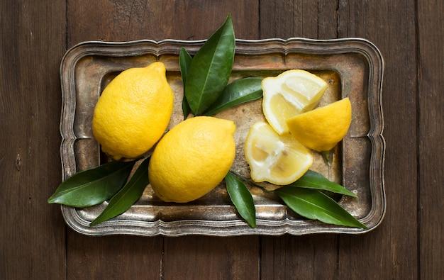Свежие лимоны на подносе на деревянном столе