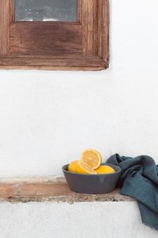 Свежие лимоны на столе на миске