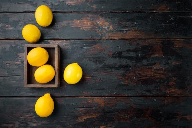 나무 상자에 있는 신선한 레몬 세트, 어두운 나무 배경, 위쪽 뷰 플랫 레이, 카피스페이스 및 텍스트 공간