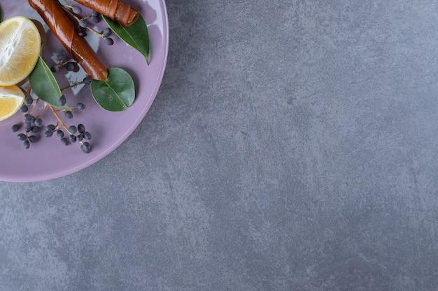 회색 배경 위에 보라색 접시에 신선한 레몬 조각.