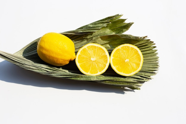 Fresh lemons in tropical palm dry leaves on white surface