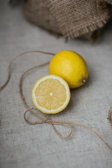 Свежие лимоны с мешками на столе. фото высокого качества