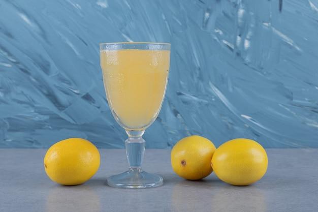 Limoni freschi con un bicchiere di succo di limone. sulla superficie grigia
