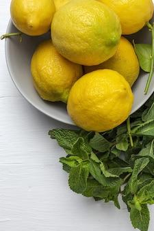 Свежие лимоны с зелеными листьями мяты сверху. плоская планировка