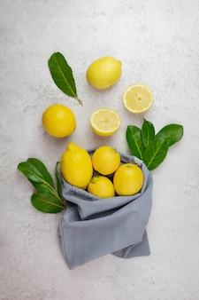 Свежие лимоны с листьями в льняном мешочке на светло-сером бетоне