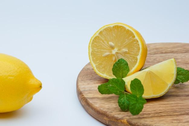 Limoni freschi con le foglie su bianco e sul tagliere