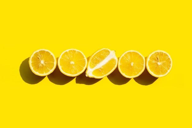 Fresh lemons on yellow surface