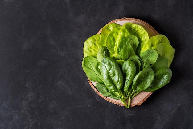 Свежий салат и шпинат на деревянной доске