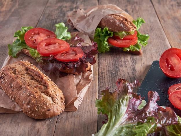新鮮なレタスとトマトのスライス、パンのバゲット、木製のテーブルで隔離