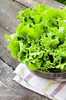 Свежие листья салата в металлической миске на старый деревянный стол