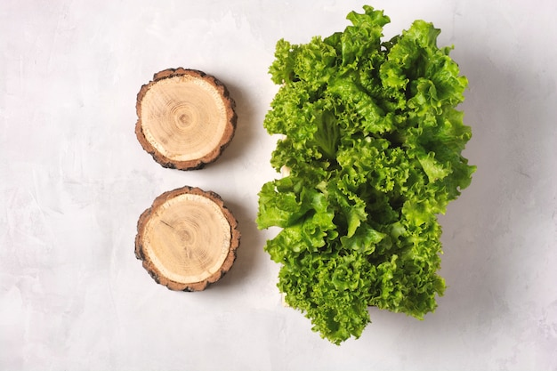Fresh lettuce leaves in a wooden box on a gray