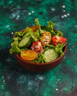 Fresh lettuce salad with yellow tomatoes, slices,cherry tomatoes,seeds bowl on dark,