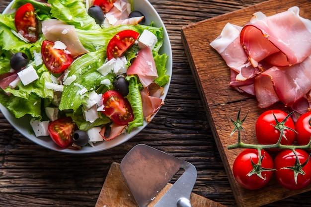 Салат из свежего салатаполезный средиземноморский салат с оливками, помидорами, пармезаном и ветчиной прошутто