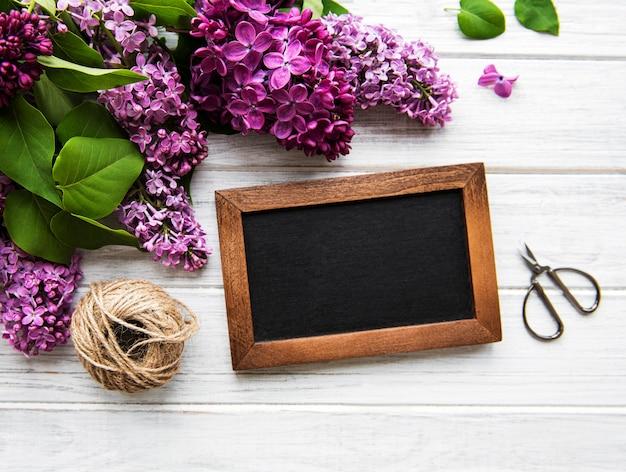 黒板にコピースペース、フラットレイ花の構成で木製の背景の上に新鮮なライラックの花のフレーム