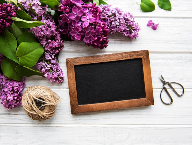 Fresh lilac flowers frame over wooden background with copy space on blackboard, flat lay floral composition