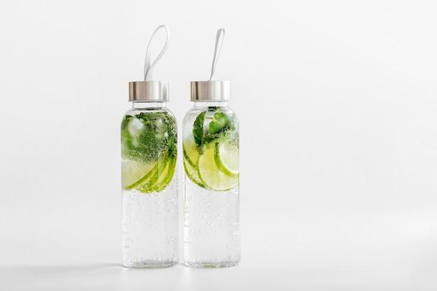 Свежая вода с добавлением лайма и мяты, коктейль, детокс-напиток, лимонад в многоразовых бутылках. летние напитки. концепция здравоохранения.