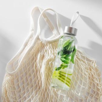 신선한 라임과 민트가 주입된 물, 칵테일, 해독 음료, 에코백이 있는 재사용 가능한 병에 담긴 레모네이드. 친환경. 지속 가능한 라이프 스타일.