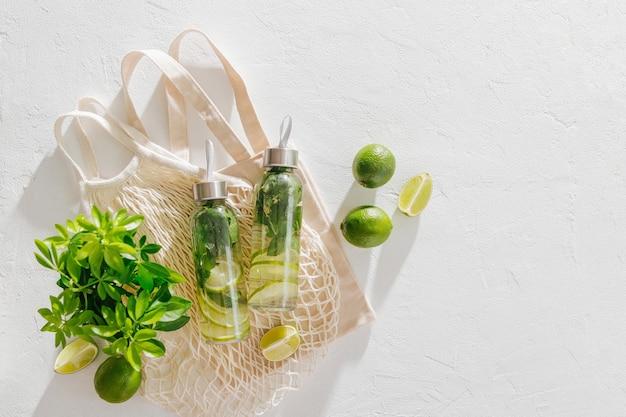 신선한 라임과 민트가 주입된 물, 칵테일, 해독 음료, 에코백이 있는 재사용 가능한 병에 든 레모네이드. 친환경. 지속 가능한 라이프 스타일.