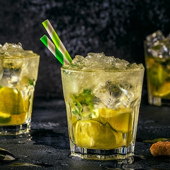 Fresh lime cocktail with ice on dark.