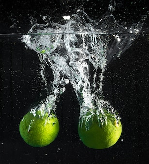 Fresh lime falling in water