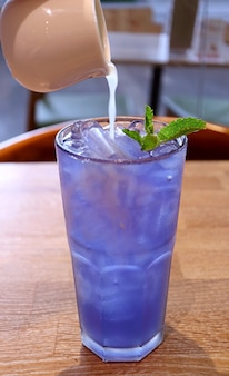 Fresh lime juice being added into iced butterfly pea flower tea created color changing