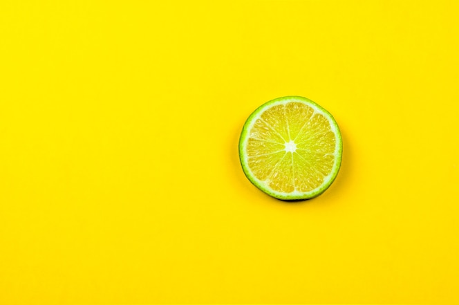 Fresh lime slice on bright yellow background