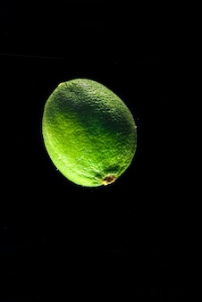 Fresh lime in water isolated on black