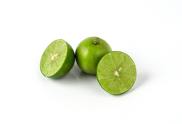 Fresh lime with half and leaves on white