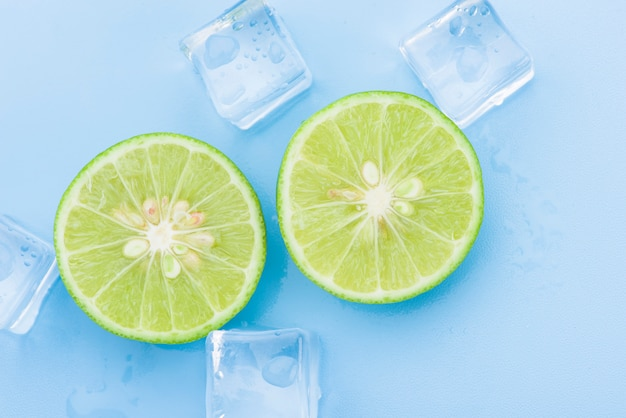 Fresh lime with ice cube on blue