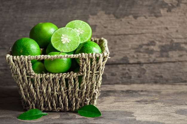 Fresh limes in the basket on a wooden background