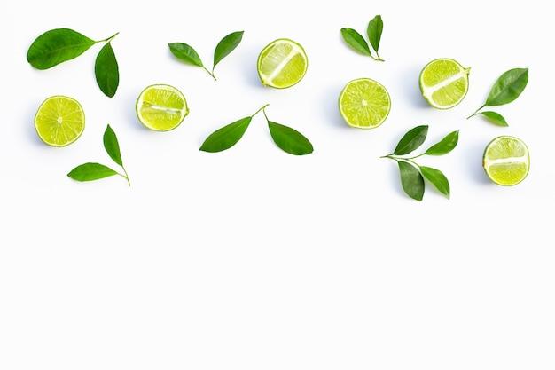 Свежие лаймы с зелеными листьями на белом фоне. вид сверху